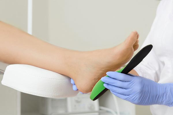 Picture of a podiatrist fitting an orthotic onto a foot